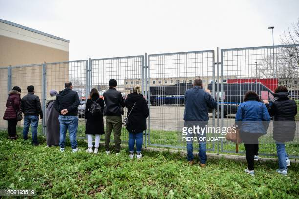 Inmates' relatives standing outside peek into the Sant'Anna prison in Modena, Emilia-Romagna, as they gather to protest measures including a ban on...