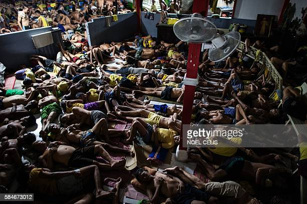 Inmates sleep on the ground inside the Quezon City jail at night in Manila in this picture taken on July 21 2016 There are 3800 inmates at the jail...