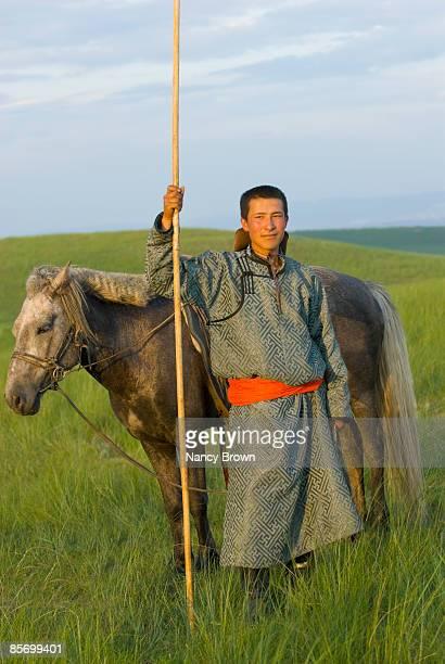 Inner Mongolia Horseman in grasslands holding uurg