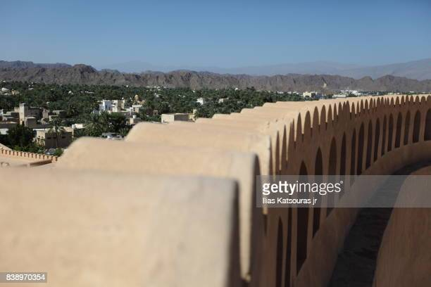 Inner wall of Nizwa sandstone castle with oasis town and the Hajar mountains in the background