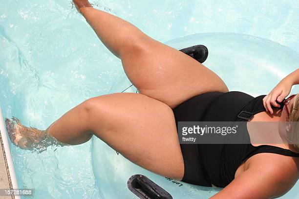 innertubing - fat blonde women stock photos and pictures