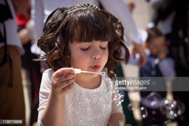 innocent girl blowing bubbles - andrea rizzi stockfoto's en -beelden