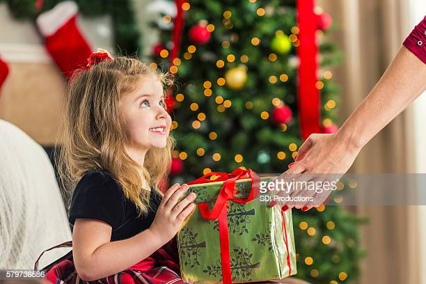 Innocent little girl happy to be handed her Christmas gift