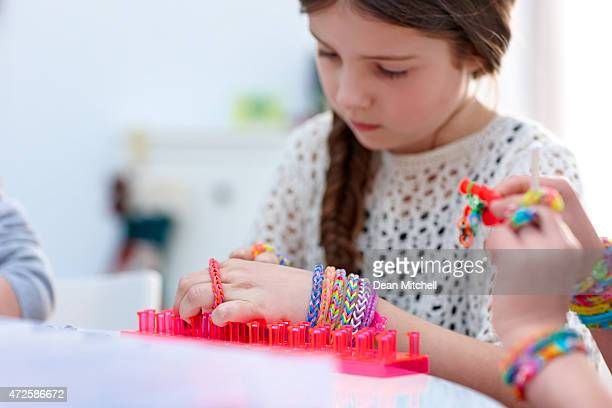 Innocent young girl making loom bands