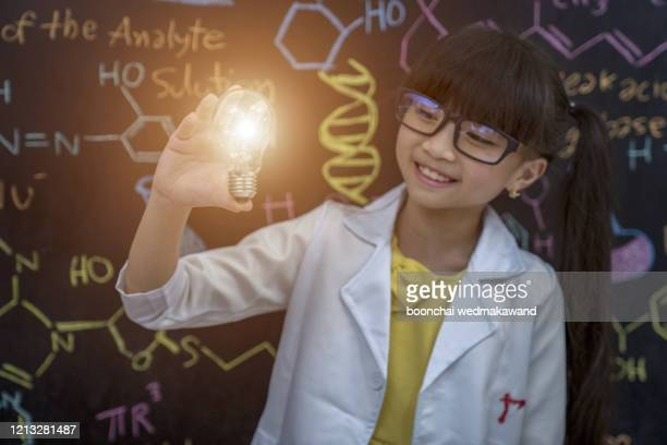 innovative creative ideas for copyright law concepts with children, reading books, surprise with light bulbs in the laboratory - science photo library stock pictures, royalty-free photos & images
