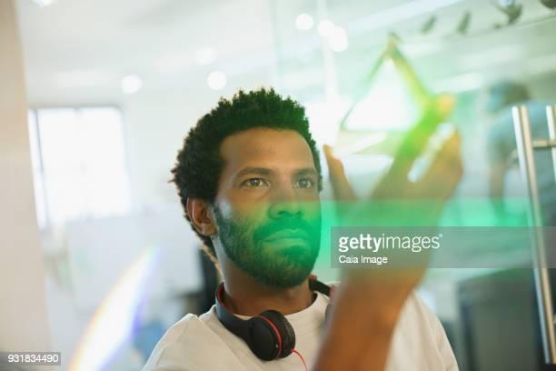 Innovative male entrepreneur examining glass cube prototype