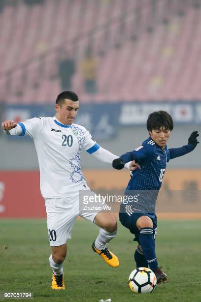 Inoue Shion of Japan and Tursunov Dostonbek of Uzbekistan in action during AFC U23 Championship Quarterfinal between Japan and Uzbekistan at Jiangyin...