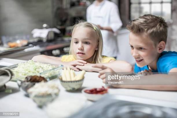Inquisitive boy and girl in kitchen