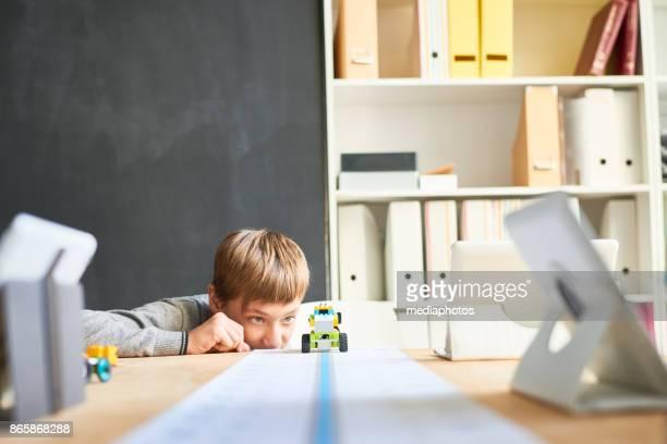 Neugierige junge spielt mit Spielzeug