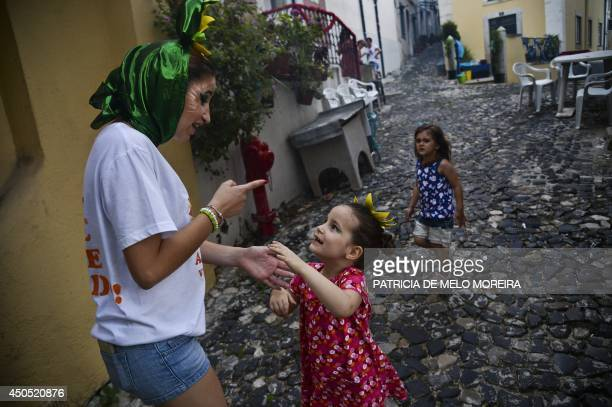 Inês Carvalho talks with a little girl at Alfama neighborhood in Lisbon on June 12 2014 Carvalho is one of the revelers from the Alfama march and...