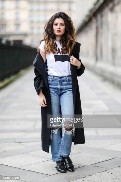 Insaf Bennis fashion blogger from Sparkles in Paris wears a Levi's white tshirt with a Paris logo Levi's blue denim ripped jeans pants Mango black...