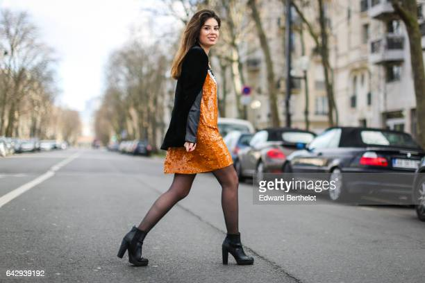 Insaf Bennis fashion blogger from Sparkles in Paris wears a Zara orange dress a Stradivarius black jacket and HM boots on February 18 2017 in Paris...