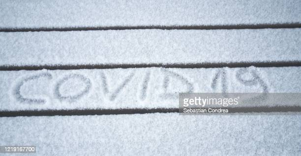 inscription - covid-19 the virus made on snow texture. - coronavirus winter stock pictures, royalty-free photos & images