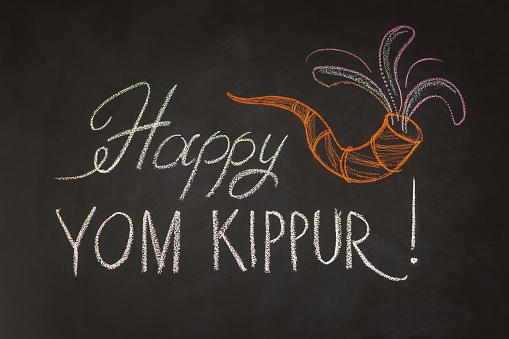 Inscription Happy Yom Kippur and symbol Rosh Hashanah on chalkboard background. 1169343182