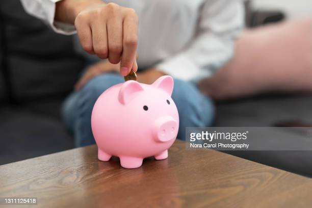 inserting coin into piggy bank - mortgage stock pictures, royalty-free photos & images