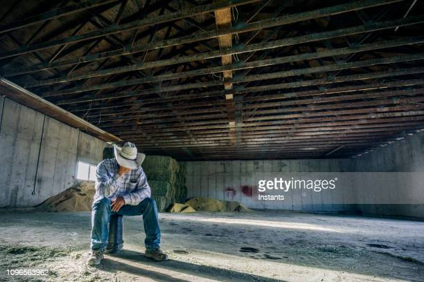 inside a barn, a desperate looking man sitting all by himself on a bucket. - crisis stock pictures, royalty-free photos & images