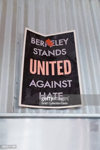 Inside a restaurant workers have used a magnet to hang a poster reading Berkeley Stands United Against Hate on the metal hood of a stove part of a...