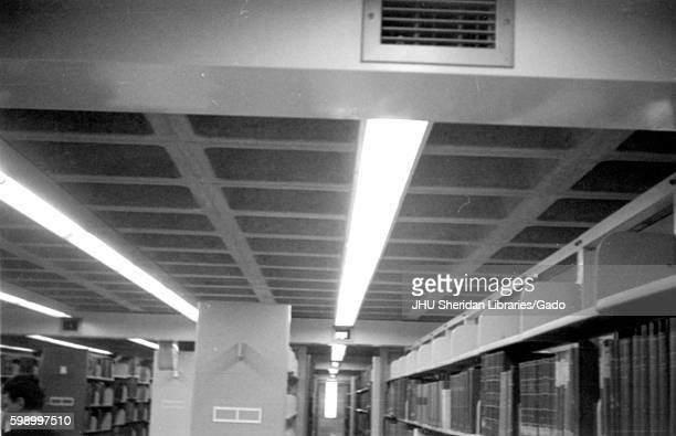 Inside a stack level of Milton S Eisenhower Library at Johns Hopkins University, rows of books stand from floor to ceiling, with long beams of lights...
