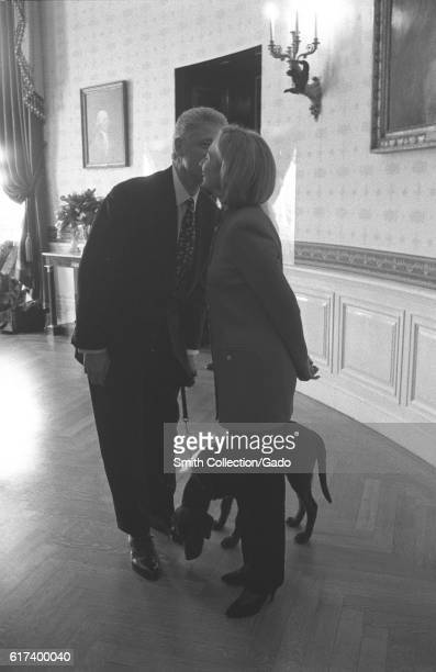 Inside a White House dining room President Bill Clinton stands beside First Lady Hillary Rodham Clinton both wearing pant suits smiling while...