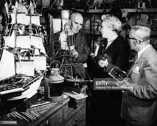 Inside an antique shop a man is showing an old lantern to a couple of interested customers Montreal Quebec Canada 1955 Photo taken during the...