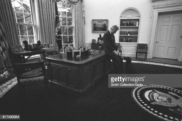 Inside his Oval Office President Bill Clinton rests against his desk with his hands in his lap looking down at First Pet Buddy the dog a mocha brown...