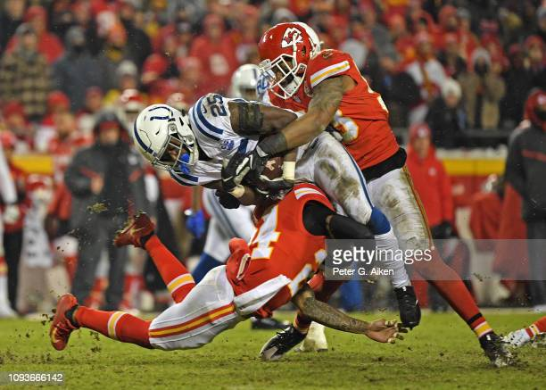 Inside linebacker Anthony Hitchens and strong safety Jordan Lucas of the Kansas City Chiefs tackles running back Marlon Mack of the Indianapolis...