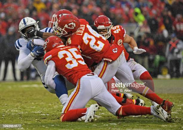 Inside linebacker Anthony Hitchens strong safety Jordan Lucas and cornerback Charvarius Ward of the Kansas City Chiefs tackle tight end Eric Ebron of...
