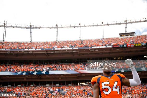 Inside linebacker Brandon Marshall of the Denver Broncos stands and holds a fist in the air during the national anthem before a game against the...