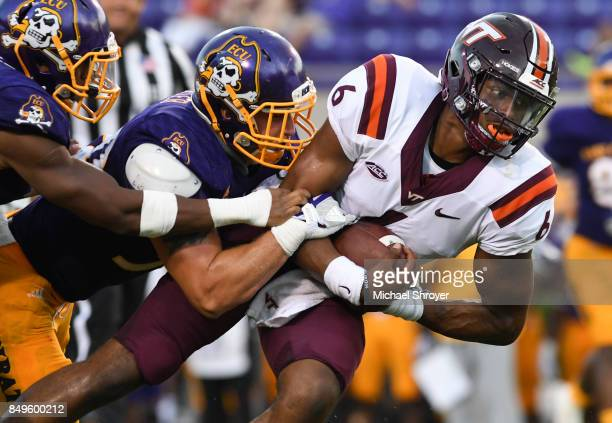 Inside linebacker Joe Carter of the East Carolina Pirates tackles quarterback AJ Bush of the Virginia Tech Hokies in the second half at DowdyFicklen...