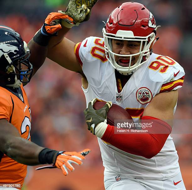 Inside linebacker Josh Mauga of the Kansas City Chiefs fends off running back CJ Anderson of the Denver Broncos after intercepting Peyton Manning in...