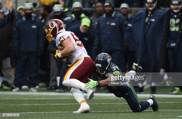 Inside linebacker Will Compton of the Washington Redskins intercepts a pass in front of running back Thomas Rawls of the Seattle Seahawks during the...