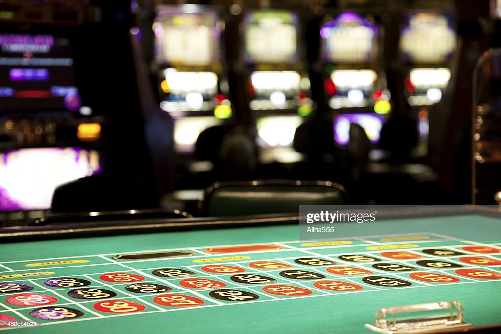 Inside of a casino, roulette table and slot machines : Stock Photo