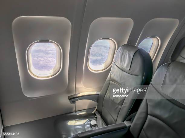 Inside of a plane overlooking some chairs and windows
