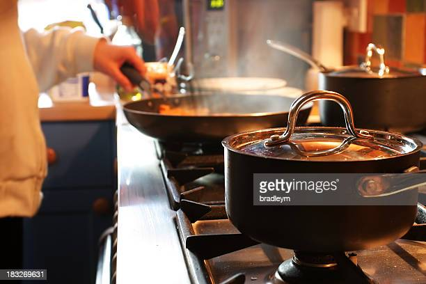 Inside of a restaurant kitchen focusing on the cooking pans