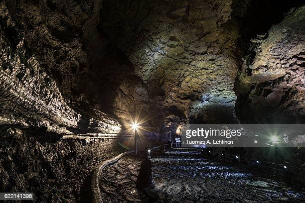inside the dark, lit and empty manjanggul lava tube cave on jeju island in south korea. - jeju island stock pictures, royalty-free photos & images