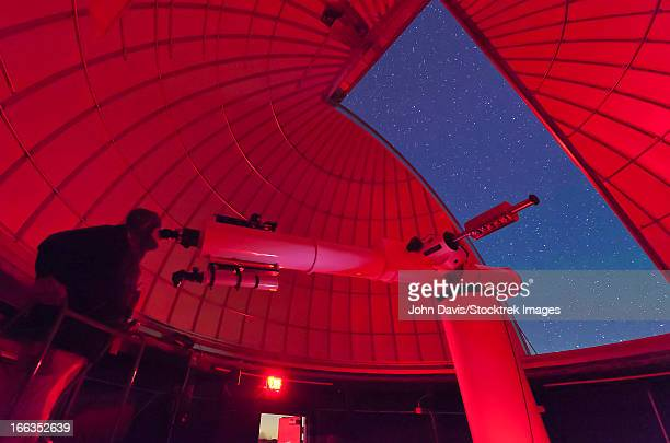 Inside the observatory, an astronomer makes observations with a large refractor telescope at the 3RF astronomy campus in Texas.