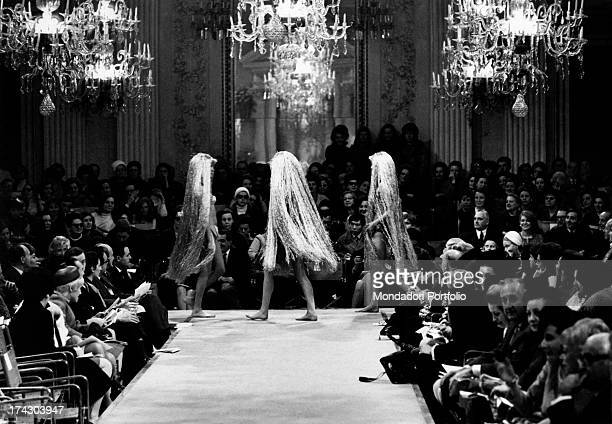 Inside the Pitti Palace two models parade holding hands they wear the same type of very daring evening wear in male and female versions Florence...