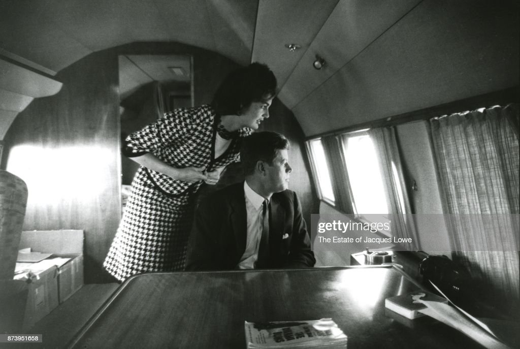 Inside their private plane (nicknamed the 'Caroline,' after their daughter), married couple (future US First Lady) Jacqueline Kennedy (nee Bouvier, 1929 - 1994) and Senator (and future US President) John F Kennedy (1917 - 1963) looking out a window at supporters on the tarmac during a campaign stop, California, Spring 1960.