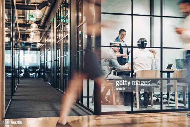 inside view of an office building with blurred motion - teamwork stock pictures, royalty-free photos & images
