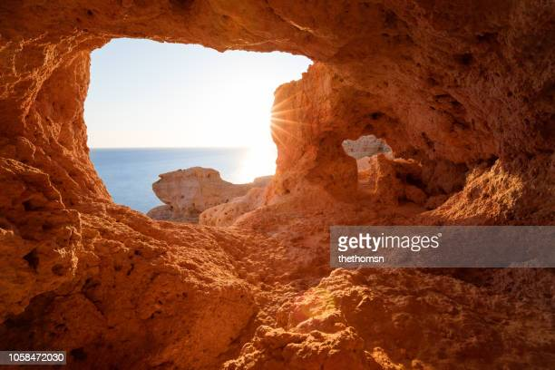 inside view of rocky red colored cave on coast during sunset, algar seco, algarve, portugal - エウロパ ストックフォトと画像