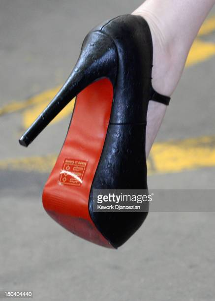 InsideEdition television reporter Brianna Deutsch puts on a pair of counterfeit Louboutin pumps and high heels featuring the distinctive red sole of...