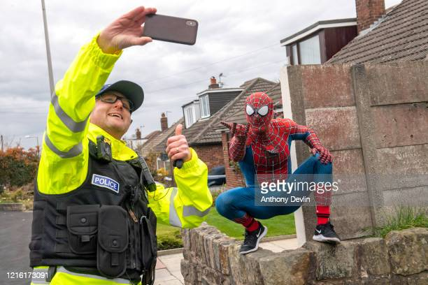 Inspector Alex Taylor from Greater Manchester Police takes a selfie with Jason Baird dressed as Spider-Man as he walks the streets of Bredbury to...