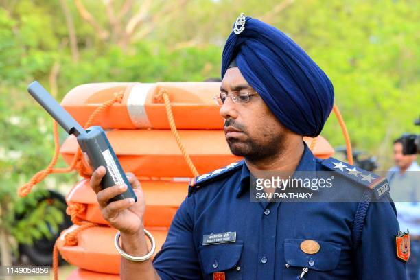 Inspector at India's 6th National Disaster Response Force Baljit Singh Sodhi checks a satellite phone at a NDRF camp in Chiloda some 40 kms from...