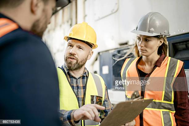 Inspector discussing with colleagues in shipyard