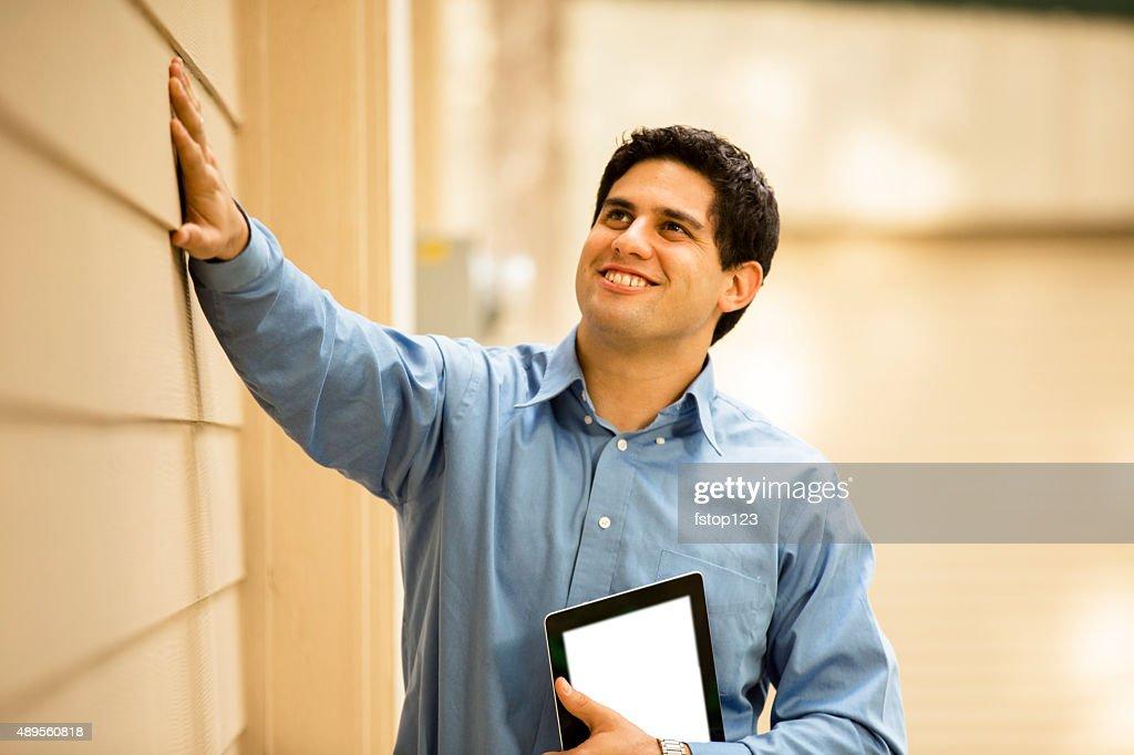 Inspector, engineer examines building wall, window outdoors.  Digital tablet. : Stock Photo