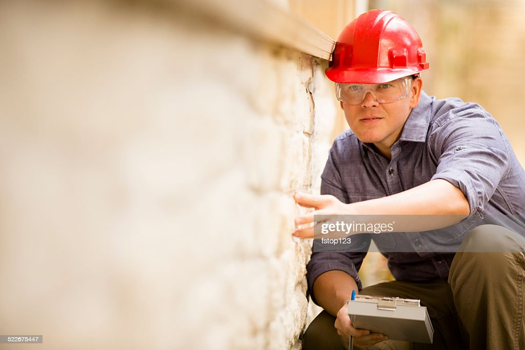 Inspector or blue collar worker examines building wall outdoors. : Stock Photo