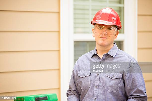 Inspector or blue collar workers examines building wall. Outdoors.
