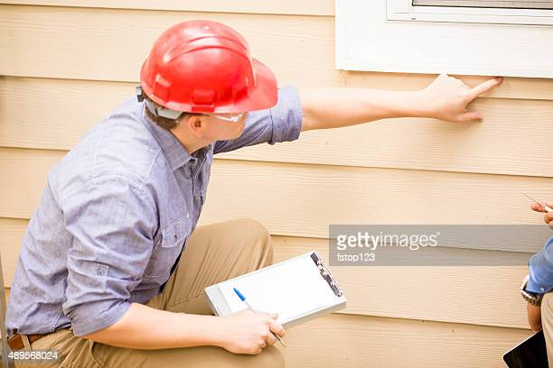 Inspector or blue collar workers examines building wall, window. Outdoors.