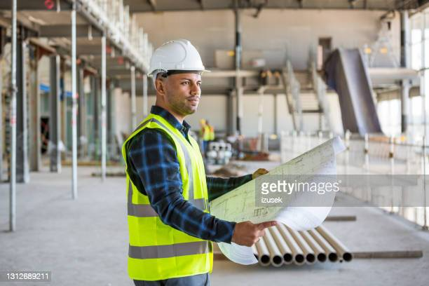 inspector standing at the construction site - izusek stock pictures, royalty-free photos & images