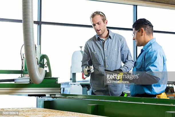 Inspector talks with employee in workshop
